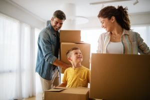 Happy family unpacking boxes in new home on moving day