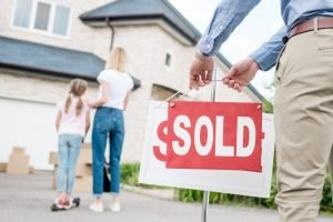 partial view of realtor hanging sold sign in front of people moving into new house