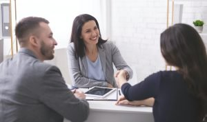 Positive insurance broker handshaking with young couple